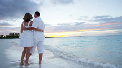 Happy Caucasian barefoot couple enjoying a beach vacation at sunset - stock footage