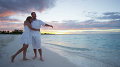 Young Caucasian couple on a luxury vacation beach at sunset - stock footage