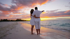 Happy young Caucasian couple enjoying a beach vacation at sunset - stock footage