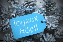 Blue Label On Fir Cones Joyeux Noel Means Merry Christmas Stock Photos