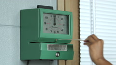 Hand putting time card in punch clock and clocking in - stock footage
