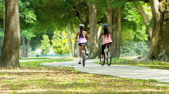 Young happy multi ethnic American girls cycling to keep active Stock Footage