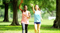 Young happy multi ethnic American girls power walking to keep healthy - stock footage