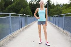 Confident female runner having her break after running - stock photo