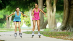 Young happy multi ethnic American girls enjoying roller skating outdoor - stock footage