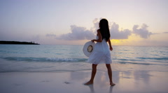 Barefoot Asian Chinese girl at sunset on tropical beach - stock footage
