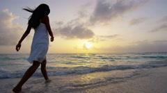 Asian American girl walking barefoot at sunset Stock Footage