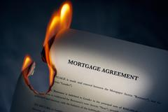 Stock Photo of Mortgage Agreement Contract Burning On Fire