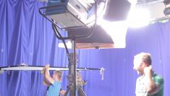 Stock Video Footage of Members of the crew installs the lighting equipment on the set