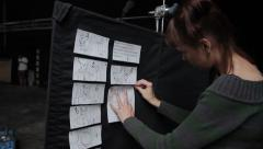 The girl prepares a Board with storyboards of the film. Film production Stock Footage