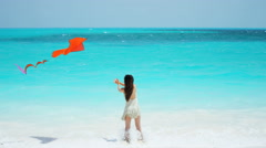 Barefoot Asian Chinese girl on beach playing with kite - stock footage