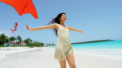 Young ethnic Asian Chinese girl with red kite on beach - stock footage