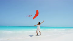 Barefoot African American girl on beach playing with kite - stock footage