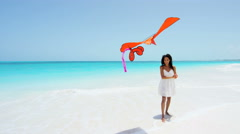 Barefoot African American girl on beach playing with a kite - stock footage
