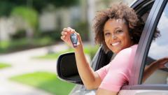 Portrait of young pretty African American female smiling holding car key in car - stock footage