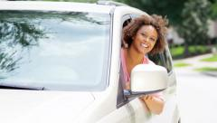 Portrait of young happy African American female in rental car on vacation - stock footage
