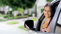Portrait of young happy Indian American female taking driving lessons in car - stock footage