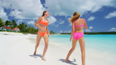 Young Caucasian sisters in swimwear on a luxury island beach - stock footage