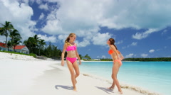 Happy young female Caucasian children in swimwear on a tropical beach - stock footage