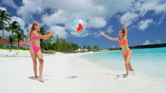 Happy young female Caucasian children in swimwear playing with a beach ball - stock footage