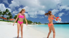 Young Caucasian sisters in swimwear playing with a beach ball - stock footage