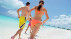Loving Caucasian family in swimwear on a tropical beach vacation - stock footage