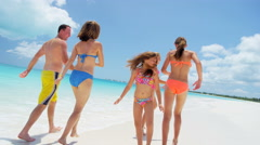 Caucasian family wearing swimwear barefoot on a beach together Stock Footage