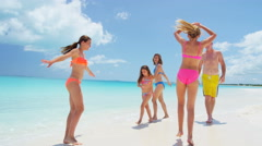 Young Caucasian parents and daughters in swimwear on a beach Stock Footage