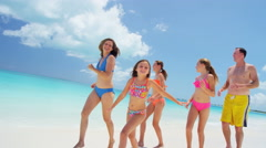 Young Caucasian parents and daughters in swimwear on a beach - stock footage