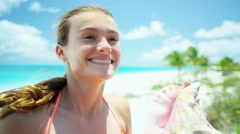 Portrait of a pretty Caucasian teenager on a tropical beach with conch shell - stock footage