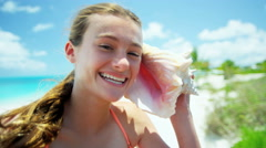 Portrait of smiling Caucasian girl on a beach holding a conch shell - stock footage