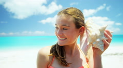 Portrait of a Caucasian teenage girl on a beach holding conch shell - stock footage