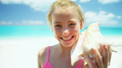Portrait of a blonde Caucasian girl on a beach holding conch shell - stock footage