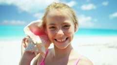 Portrait of a blonde female girl on a beach with a conch shell - stock footage