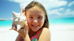 Portrait of a cute female Caucasian child on a beach with a conch shell - stock footage