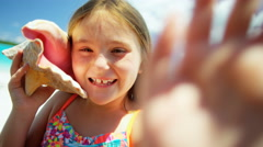 Portrait of a little Caucasian girl on a vacation beach with a conch shell - stock footage