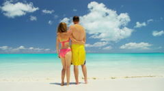 Barefoot Caucasian couple in swimwear on a tropical beach - stock footage