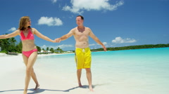 Young Caucasian couple in swimwear walking on a Caribbean beach - stock footage