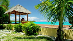 Caucasian couple sitting in a tiki beach hut - stock footage
