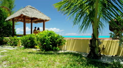 Young Caucasian couple sitting in thatched tiki hut on a Caribbean beach - stock footage