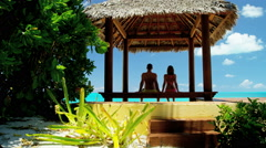 Caucasian couple sitting in a Caribbean tiki hut - stock footage