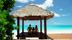 Caucasian family sitting in a tiki beach hut Stock Footage