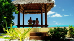 Young Caucasian family sitting in thatched tiki hut on a beach - stock footage