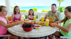 Young Caucasian family dining on vacation beach hotel decking Stock Footage