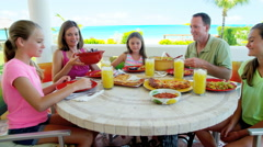 Caucasian family dining outdoors at a beach resort Stock Footage