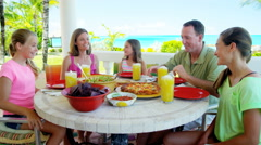 Young Caucasian family in casual clothing eating outdoors by a beach Stock Footage