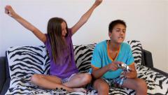 Brother and sister playing video game, girl wins and celebrates, dolly shot, 4k. Stock Footage