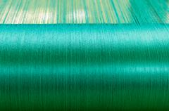 Green silk on a warping loom of a textile mill - stock photo