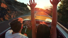 Happy Couple Driving Classic Convertible Car into Sunset on Country Road - stock footage