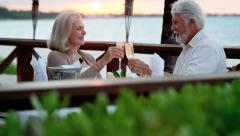 Caucasian senior couple enjoying evening beachfront dining - stock footage